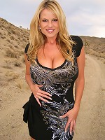 Kelly wears a little black dress and gives a blowjob in the desert.