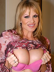 Kelly in bright pink lingerie spits on her red dildo and works her pussy.