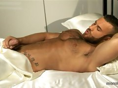 Muscled gay bear Gianluigi poses on the bed and strokes his cock