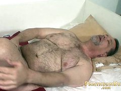 Hairy mature bear strokes his dick on the bed