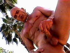 Buff and tanned bald old man pulls on his pecker by the pool to get himself off