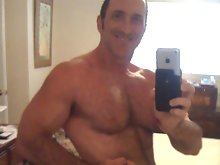 Big muscled dude lifts weight and shows his hairy chest