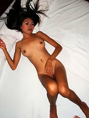 Petite Thai girlfriend with nice natural tits lies on a bed naked
